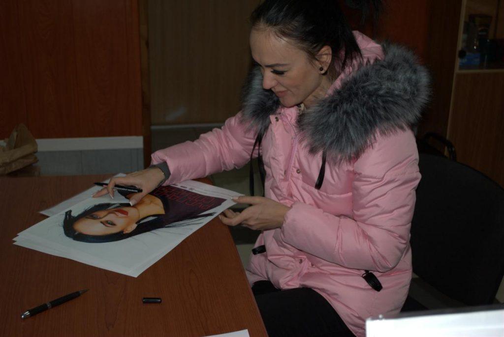 Руслана Собиева подписывает постеры для своих поклонников